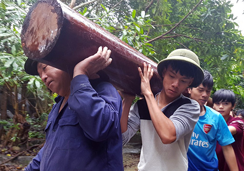 Công nhân di chuyển nhiều trụ gỗ tại khu biệt phủ đang tháo dỡ. Ảnh: Đ.X.
