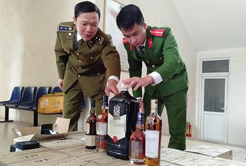 Lực lượng chức năng kiểm tra lô rượu nhập lậu. Ảnh: Lam Sơn.