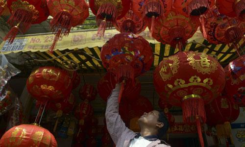Một người đàn ông xem những chiếc đèn lồng kiểu Trung Quốc tại một cửa hàng ở Phnom Penh. Ảnh: AFP.