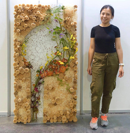 Quỳnh Giang bên bức tường hoa đoạt giải vàng tại lễ hội hoa năm 2018 của Malaysia. Ảnh: NVCC.