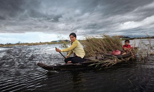 Hai mẹ con chèo thuyền trên Biển Hồ. Ảnh: NYT.