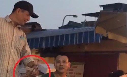 Công khai nhận tiền bảo kê ở chợ Long Biên. Ảnh: Cắt từ video VTV.