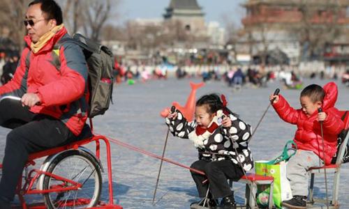 Trẻ con chơi đùa cùng người lớn tại một quảng trường ở Trung Quốc. Ảnh: AFP.