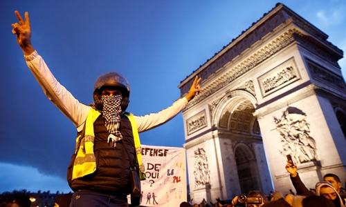 Người biểu tình áo vàng đứng trước Khải Hoàn Môn ở Paris ngày 22/12/2018. Ảnh: Reuters.
