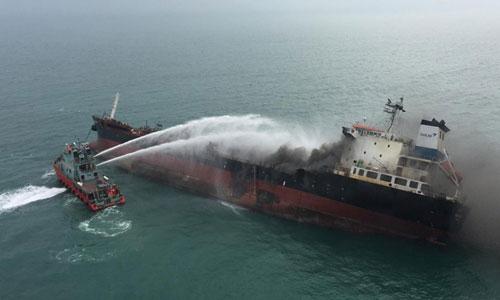 Tàu cứu hỏa Hong Kong phun nước lên tàu dầu Aulac Fortune để chữa cháy. Ảnh: SCMP.