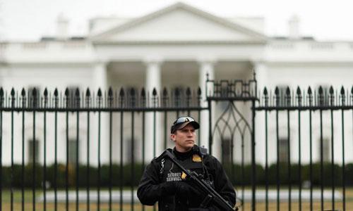Một mật vụ Mỹ mang vũ khí canh gác bên ngoài Nhà Trắng. Ảnh: Reuters.