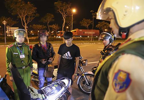 Nam thanh niên tàng trữ bình xịt hơi cay bị cảnh sát khống chế. Ảnh: Nguyễn Đông.