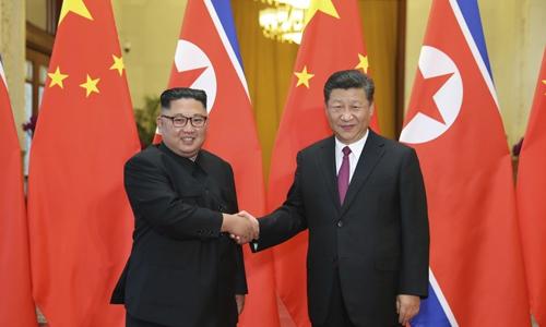 Kim Jong-un (trái)bắt tay Chủ tịch Trung Quốc Tập Cận Bình trong chuyến thăm Bắc Kinh tháng 6/2018. Ảnh: AP.