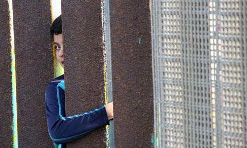 Một cậu bé Mexico nhìn qua hàng rào biên giới với Mỹ năm 2016. Ảnh: AFP.