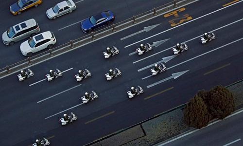 Lực lượng cảnh sát dẫn đầu đoàn hộ tống chiếc xe được cho là chở lãnh đạo Triều Tiên Kim Jong-un trên đường phố Bắc Kinh ngày 9/1. Ảnh: AP.