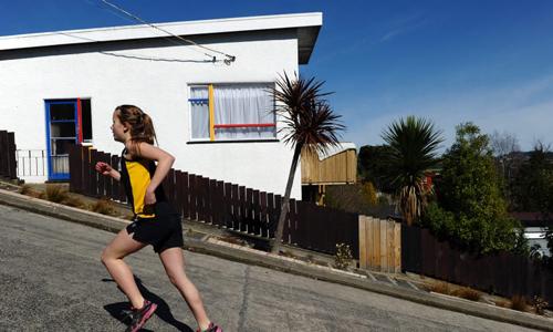Một cư dân tại thành phố Dunedin chạy bộ trên đường Baldwin. Ảnh: AFP.