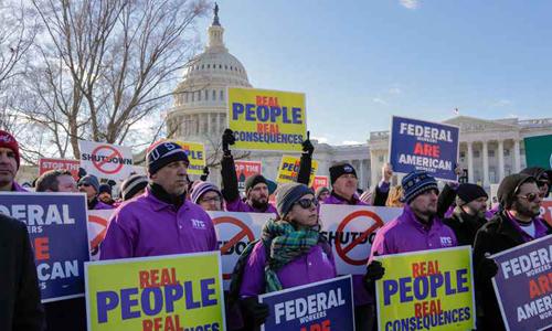 Các nhân viên liên bang cầm khẩu hiệu đòi mở cửa chính phủ. Ảnh: AP.