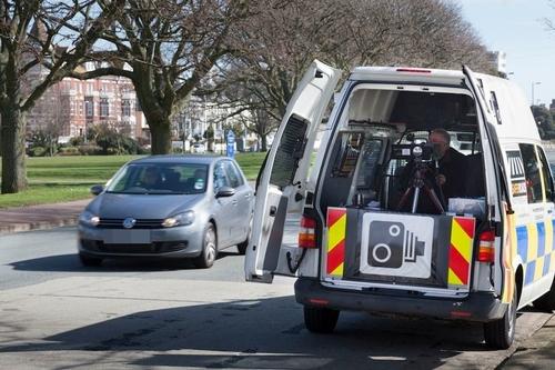 Cảnh sát lập chốt bắn tốc độ di động đằng sau xe. Ảnh: Getty.