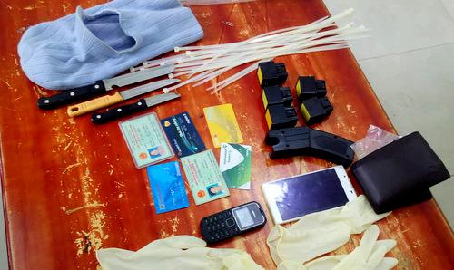 Súng điện, dao, găng tay...nghi can dùng để cướp. Ảnh: Quang Bình.