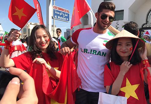 Hai cổ động viên Việt Nam chụp ảnh cùng cổ động viên Iran tại sân Al Nahyan.