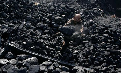 Một người đàn ông xếp than lên xe đẩy tại khu mỏ ở tỉnh Thiểm Tây, Trung Quốc. Ảnh: Reuters.