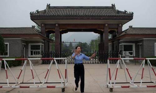 Một nữ cảnh sát cố gắng ngăn cản phóng viên chụp ảnh trước cửa vào nhà tù Tần Thành. Ảnh: AFP.