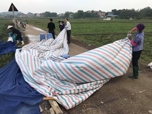 Người dân thu dọn lều bạt rời khỏi vị trí chốt chặn lối vào bãi rác. Ảnh: Gia Chính