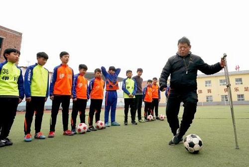 Zhang Erhu hướng dẫn học sinh kỹ thuật bóng đá vào sáng 8/1. Ảnh: Tân Hoa Xã
