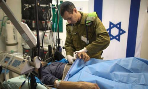 Bác sĩ quân y Israel điều trị cho một phiến quân Syria bị thương tại bệnh viện dã chiến. Ảnh: AFP.