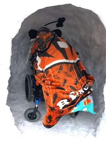 Elijah (7 tuổi) được đẩy vào lều tuyết trên chiếc xe lăn. Ảnh: Gregg Eichhorn
