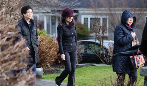 Mạnh Vãn Chu (giữa) rời nhà riêng ở Vancouver hôm 10/1. Ảnh: Bloomberg.