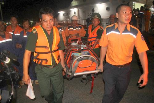 Lực lượng cứu nạn đưangư dân sức khỏe xấu từ tàu SAR 413 lên xe cấp cứu. Ảnh: Nguyễn Khoa.