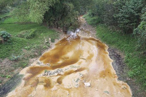Nước từ bãi rác chảy ra suối đục gầu, bốc mùi hối thối. Ảnh: Tất Định.