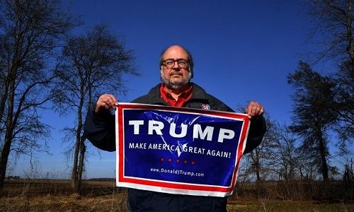 Joe Davidson cầm tấm biểu ngữ ghi câu khẩu hiệu Biến nước Mỹ vĩ đại trở lại của Tổng thống Trump. Ảnh: Washington Post.
