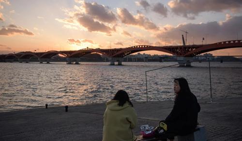 Hai thanh niên ngồi bên bờ sông Hàn, Seoul, Hàn Quốc. Ảnh: AFP.