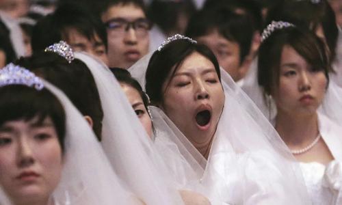 Một cô dâu ngáp dài trong lễ cưới tập thể ở Gapyeong, Hàn Quốc hồi tháng 8/2018. Ảnh: SCMP.