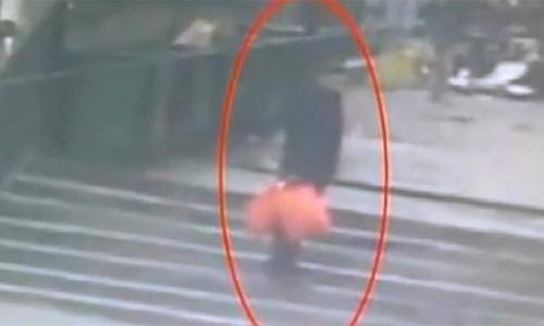 Người đàn ông xáchnhững chiếc túi đựng cặp song sinh trước khi vứt vào thùng rác ở thành phố Tây An, tỉnh Thiểm Tây, hôm 18/1. Ảnh: