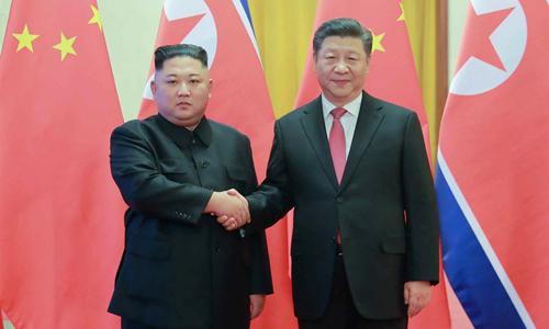 Lãnh đạo Triều Tiên Kim Jong-un (trái) bắt tay Chủ tịch Tập Cận Bình trong chuyến thăm Trung Quốc lần thứ tư hồi đầu tháng. Ảnh: Yonhap.