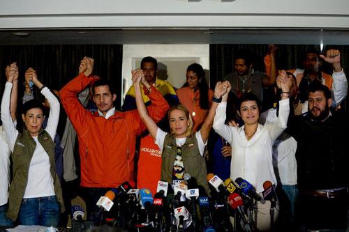 Guaido (áo đỏ, thứ hai từ trái sang) nắm tay cùng các lãnh đạo phe đối lập trong cuộc họp báo ở Caracas năm 2015. Ảnh: AFP.
