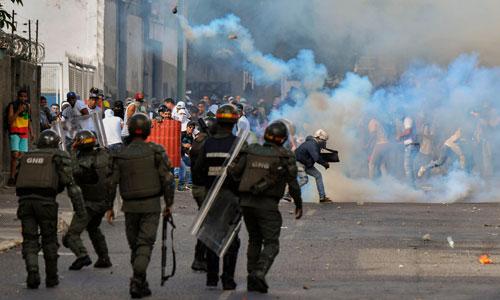 Lực lượng an ninh Venezuela bắn hơi cay vào người biểu tình hôm 23/1. Ảnh: AFP.