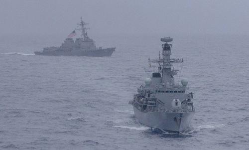 Tàu chiến Mỹ (sau) và chiến hạm Anh diễn tập trên Biển Đông. Ảnh: Reuters.