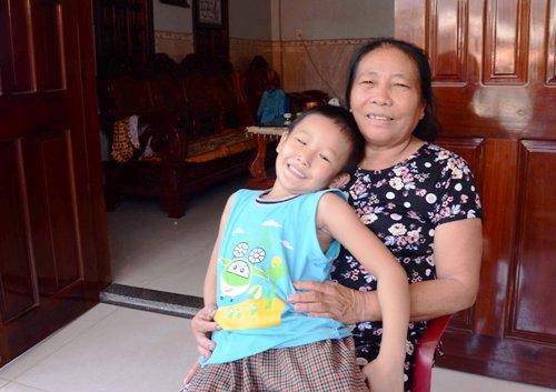 Bà Hẳn rạng rỡ ôm cháu trai trong ngôi nhà khang trang từ tiền con trai làm ở Hàn Quốc. Ảnh: Phạm Linh.