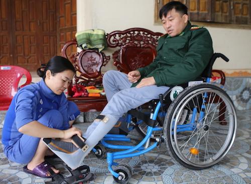 Chị Thúy hỗ trợ chồng tập phục hồi chức năng tại nhà. Ảnh: Nguyễn Hải.