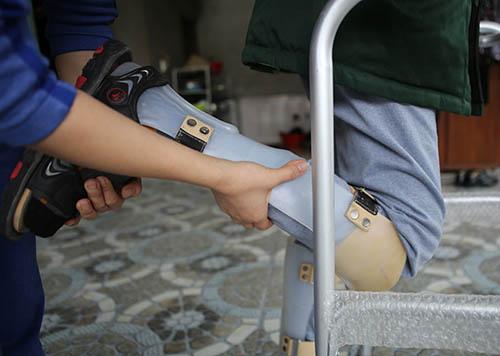 Anh Tài được người thân bóp cổ chân trong lúc luyện đi. Ảnh: Nguyễn Hải.