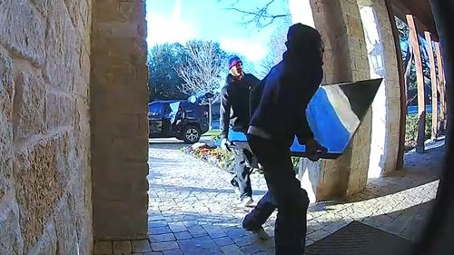 Hai kẻ trộm bất đắc dĩ mang trả chiếc tivi quá khổ. Ảnh cắt từ video.