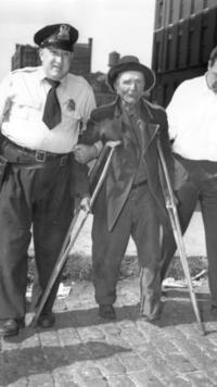 Cảnh sát Chicago dẫn giải người bị què chân về đồn vào 1954. Ảnh: Luigi Mendicino / Chicago Tribune.