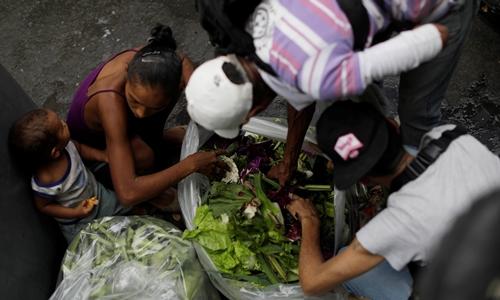 Người dân bới rác tìm thức ăn cạnh một siêu thị ở Caracas, Venezuela hôm 25/7/2017. Ảnh: Reuters.