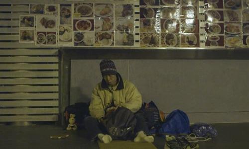 Simon Lee gà gật bên hông cửa hàng bán đồ ăn vặt trong công viên Victoria, Hong Kong. Ảnh: SCMP.