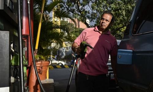 Một người bơm nhiên liệu tại trạm xăng dầu ở Caracas ngày 29/1. Ảnh: AFP.