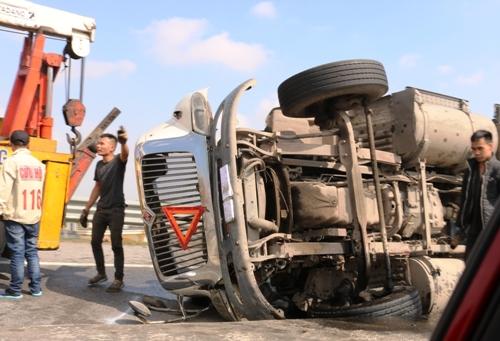 Xe đầu kéo biển 15 Hải Phòng chở 2 container hàng bị lật ngửa khi vào cua tại đường dẫn từ cao tốc Hà Nội- Hải Phòng ra quốc lộ 10, gây ùn tắc nhiều giờ. Ảnh: Giang Chinh