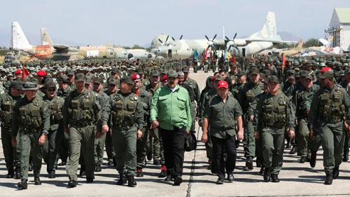Tổng thống Venezuela Nicolas Maduro (áo xanh, giữa) cùng các binh sĩ, sĩ quan quân đội tại một căn cứ quân sự. Ảnh: Reuters.