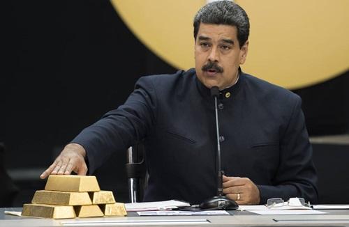 Tổng thống Maduro chạm vào các thỏi vàng trong cuộc họp với các bộ trưởng phụ trách lĩnh vực kinh tế ở Caracas tháng 3/2018. Ảnh: Reuters.
