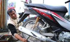 Người đàn ông cụt hai chân sửa xe trên vỉa hè