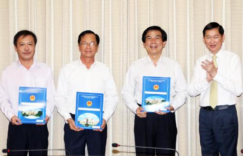 Phó chủ tịch UBND TP HCM Trần Vĩnh Tuyến (ngoài cùng bên phải) trao quyết định bổ nhiệm nhân sự BQLdự án đầu tư xây dựng các công trình giao thông vừa được lập. Ảnh: Mai Hương