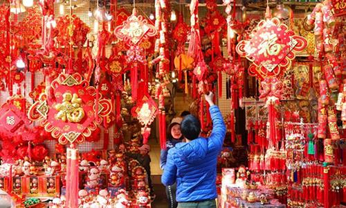 Một người Việt đang chọn đồ trang trí ngày Tết trong một khu phố ở Hà Nội hôm 1/2. Ảnh: Xinhua.